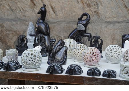 Marble Indian Figurines For Sale Outside A Tourist Street Market In India. Buddha Figurines And Shiv
