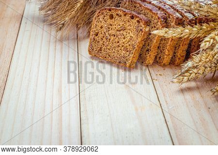 Rustic Bread. Fresh Loaf Of Rustic Traditional Bread With Wheat Grain Ear Or Spike Plant On Wooden T