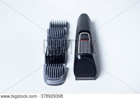 Beard Trimmer On A White Background. Different Sized Attachments Are Placed Next To The Trimmer. Bea