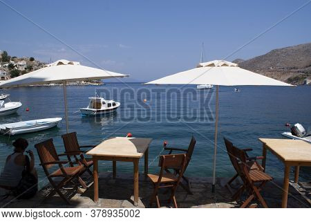Symi / Greece / August 17 2009 : The Greek Island Of Symi. Seating At A Relaxed Bar With Tables And