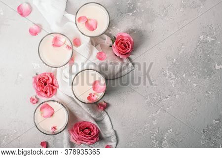 A Group Of Lunar Milk Glasses With Roses On Light Concrete. Ayurvedic Relaxing Drink For The Night.