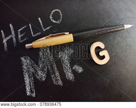 Hello Mister G Text Displayed On Chalk Board Concept With Wooden Alphabet English Symbol.