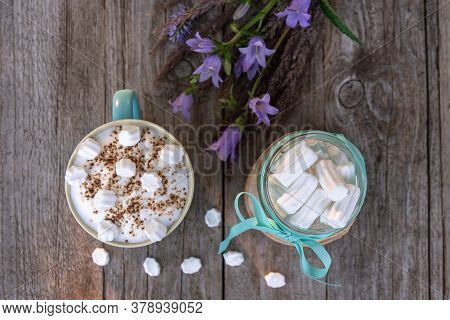 Morning Mocha With Marshmallows On A Wooden Background With Flowers.