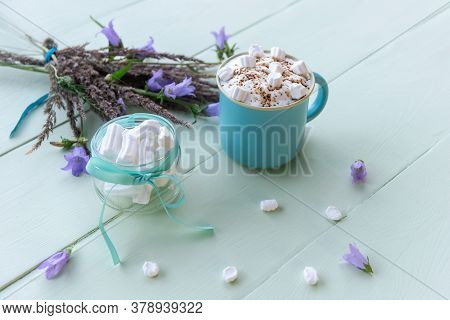Delicious Mocha With White Marshmallows On An Azure Background With Lilac Flowers.