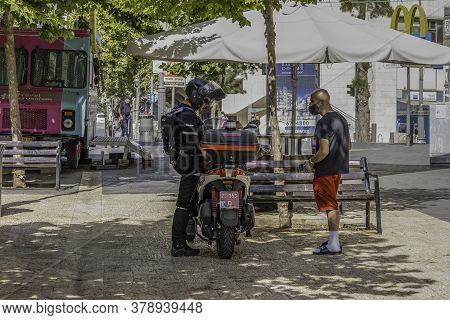 Jerusalem, Israel - July 30th, 2020: An israeli policeman interacts with a civilian on a Jerusalem, Israel, street.