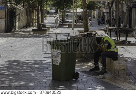 Jerusalem, Israel - July 30th, 2020: A street cleaner sitting idly on Ben - Yehuda pedestrian mall, usually a crowded main street of Jerusalem, almost empty at COVID times.