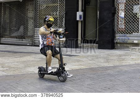 Jerusalem, Israel - July 30th, 2020: A motorized scooter rider wearing a COVID protective mask on a Jerusalem, Israel, street.