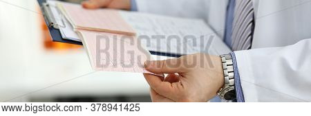 Male Medicine Doctor Hands Holding Cardiogram Chart On Clipboard Pad Closeup. Cardio Therapeutist As