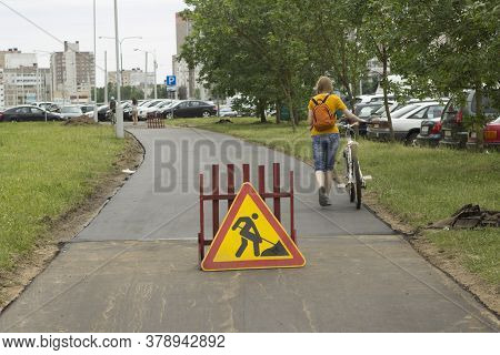 Roadworks Sign Is At The Crosswalk. Girl Cyclist Goes With A Bike On The Road Being Repaired.