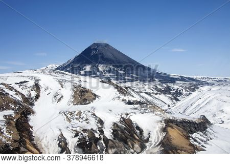 View Of The Correct Cone Of The Karymsky Volcano In The Spring After A Snowfall. Geothermal Activity