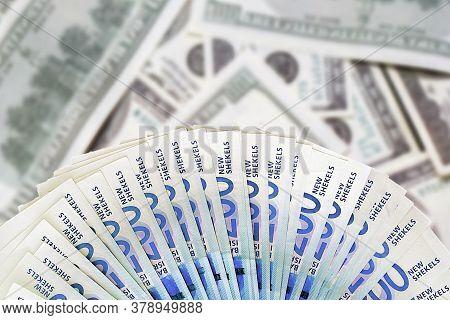 Fan New Israeli Shekel Series C. Fan Shekel Banknotes On Blur American Dollars Background.