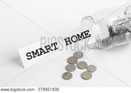 Sticking Out Of A Jar Of Coins A Piece Of Paper With A Text Smart Home On A White Background
