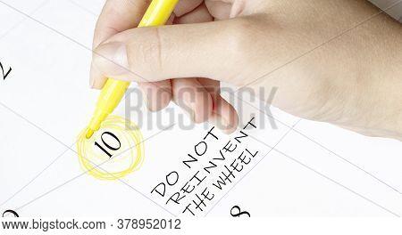 Hand Encircles A Date On A Calendar With Text Do Not Reinvent The Wheel Yellow Felt-tip Pen