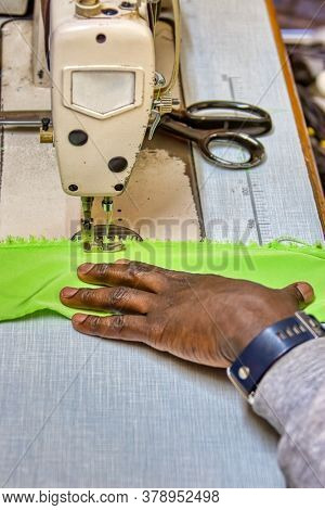 African worker in a small tailor shop, working in an industrial sewing machine