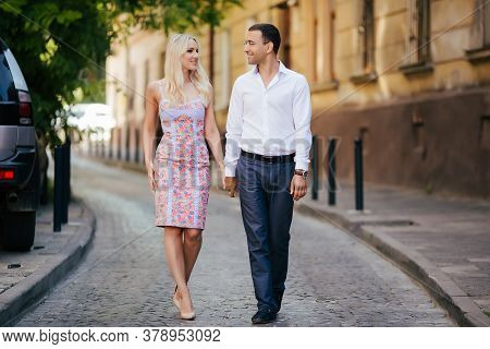 Walking Down The Street Together. Happy Young Man And Smiling Woman Walking Through The Streets Of O