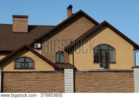Attic Of A Brown Brick House With Windows Against A Blue Sky Behind A Fence
