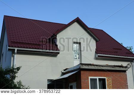 Attic Of A White Private House With A Glass Door Under A Red Tiled Roof Against A Blue Sky