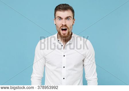 Shocked Irritated Young Bearded Man Guy 20s In White Classic Shirt Isolated On Pastel Blue Backgroun
