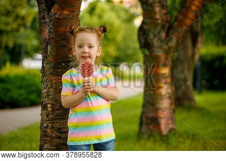 Little Girl With Red Lollipop In Summer In The Park.