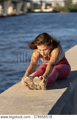 Young Fit Woman In Pink Legging Sitting On Embankment, Stretching Muscles In Seated Forward Bend Pos