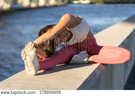 Oung Yoga Runner Woman In Pink Legging Sitting On Embankment, Stretching Muscles In Seated Forward B
