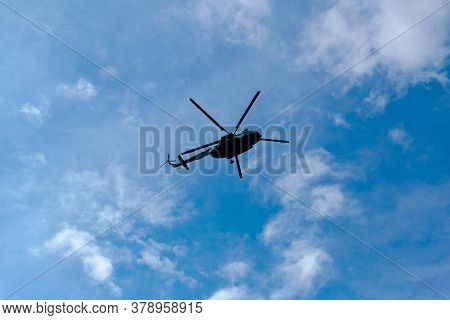 Helicopter In The Blue Cloudy Sky From Beneath