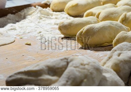 Dough On A Board With Flour And Pies. Cooking Homemade Hotcakes With Onion And Egg Filling. Selectiv