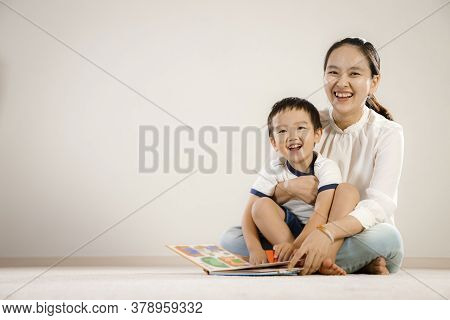 Asian Mother And Child Reading Book Together Concept. Vietnamese Mum And Son Sitting On Floor, Laugh