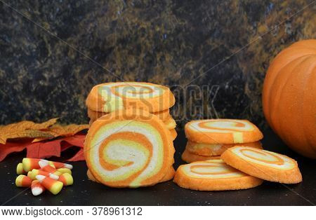 Candy Corn Swirl Cookies In A Fall Setting With Candy Corn Candies And A Pumpkin On The Side.