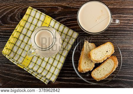 Pitcher With Milk On Checkered Napkin, Cup With Fermented Baked Milk, Pieces Of Sprinkled Horn-shape