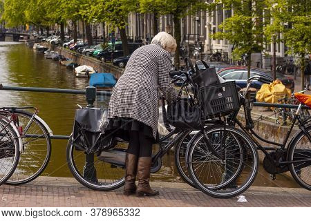Amsterdam, Netherlands 05/16/2010: A Well Dressed Elderly Woman Wearing Leather Boots And A Checkerb