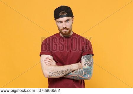 Perplexed Young Bearded Tattooed Man Guy In Casual T-shirt, Black Cap Posing Isolated On Yellow Wall