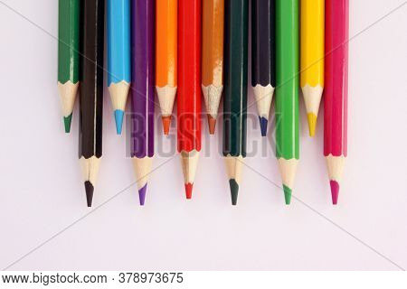 Colored Pencils On A White Background In Staggered Order. Lots Of Different Colored Pencils. Colored