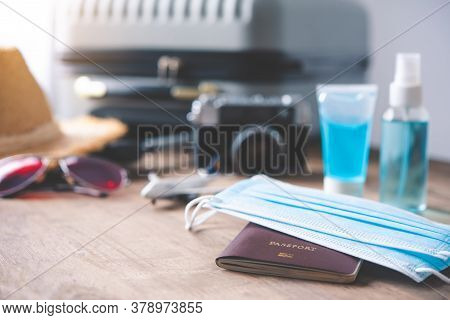 Passport Placed On A Wooden Floor With A Corona Virus Protection Device Such As Mask And Gel Mask Wi