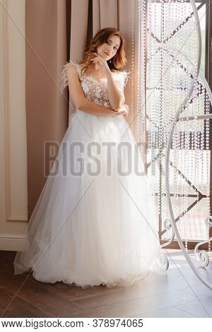 Girl With Long Hair In A Beautiful White Dress For Prom Or Wedding Party Standing At The Window.
