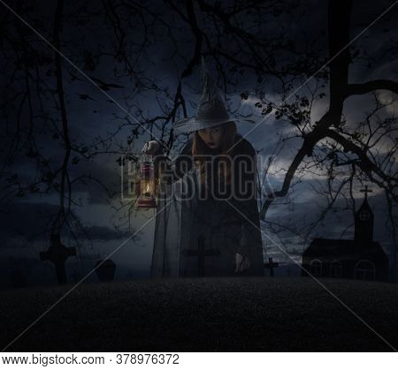 Halloween Witch Holding Ancient Lamp Standing Over Grass, Dead Tree, Cross, Birds With Church Over S