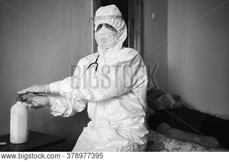 Black And White Image Of Doctor In Ppe Suit Visiting Patient At Home, Decontaminating Hands With Alc