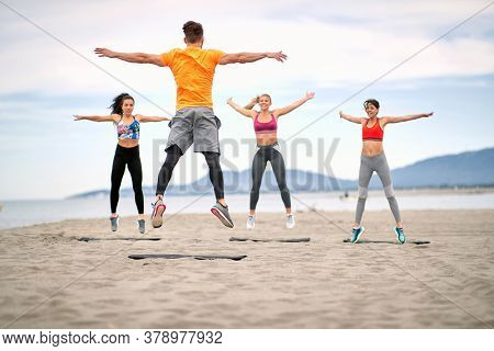 Group of fitness people jumping  and fitness workout on the beach.