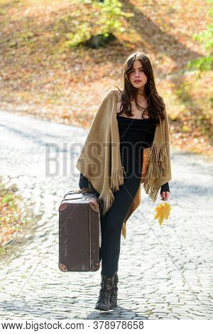 Autumn Travel. Woman Hold Retro Old Fashioned Suitcases On Autumn Leaves Background. Hipster Leaving