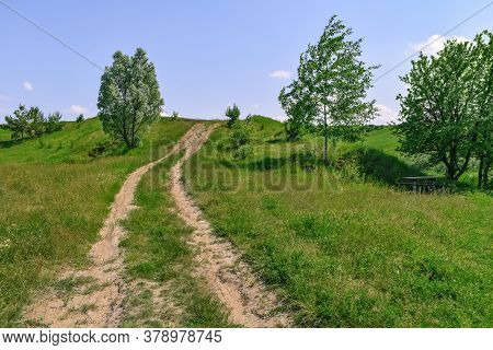 Two-lane Dirt Road Up A Hill In The Middle Of Meadows And Lush Green Grass On A Sunny Spring-summer