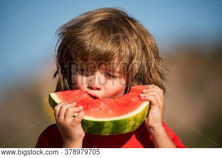 Close-up Portrait Of Cute Little Child Eating Sweet Watermelon. Portrait Of A Cute Boy Eating Water