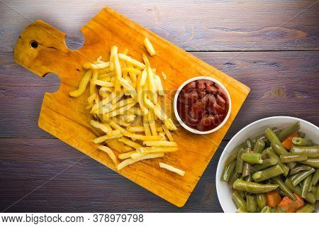 French Fries With Ketchup On Purple Wooden Background. French Fries On Brown Wooden Plate With Veget