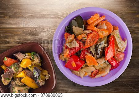 Vegetable Stew On Brown Wooden Background. Stew In Bulgarian On Purple Plate With Vegetarian Salad T