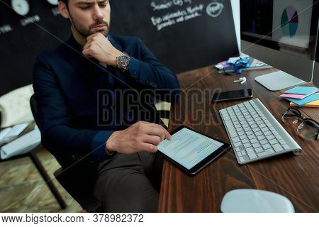 Last News. Young Businessman Man Sitting At His Workplace In The Modern Office And Reading Financial