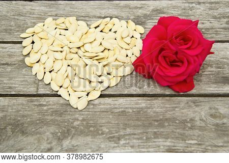 The Heart Of Pumpkin Seeds Lies On A Wooden Background Close-up. Nearby Lies A Flower Of A Scarlet R