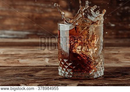 Frozen Movement Of A Splash Of Whiskey Cognac Or Brandy In A Beautiful Glass Due To A Thrown Ice Cub