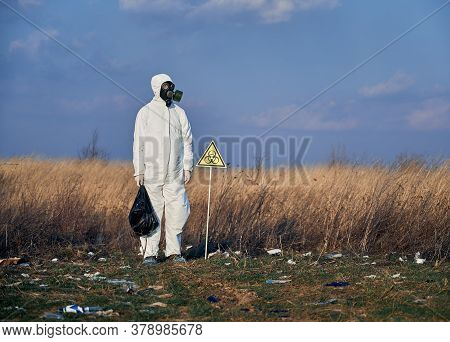 Ecologist Wearing White Protective Suit, Gas Mask, Standing In The Field Full Of Garbage, Next To A