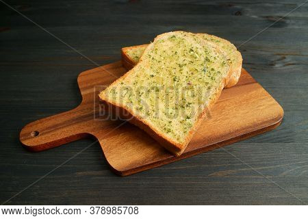 Closeup Two Crispy And Flavorful Homemade Garlic Butter Toasts On Wooden Breadboard