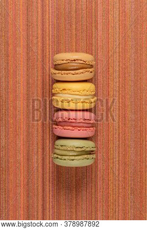 Four Colorful Sweet Macaroons On Red Vinyl Background.