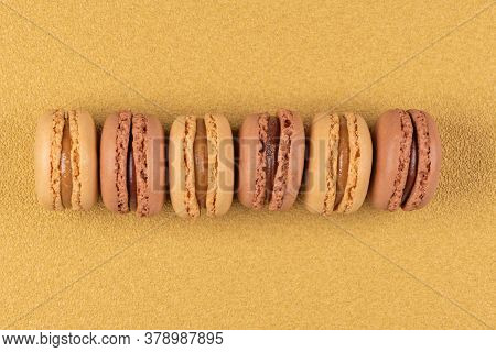 Six Coffee And Chocolated Flavoured Macaroons On Yellow Vinyl Background.